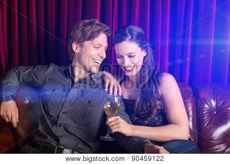 Young flirty couple with wine at a club lounge