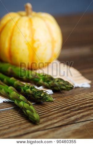 Asparagus on a mat with a pumpkin.