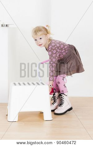 standing little girl with a stool