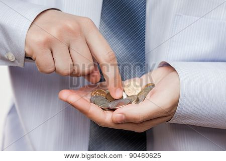 Business risks and finance issues concept - businessman hand holding coin savings counting money profit or losses