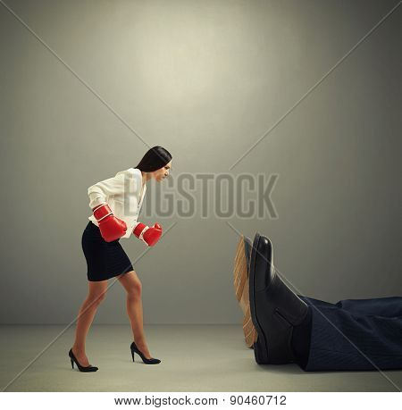 angry businesswoman in formal wear and boxer gloves looking at big knocked out man over dark grey background