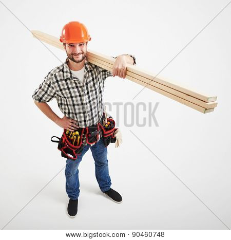 view from above on smiley builder in uniform holding long wooden boards. isolated on light grey background