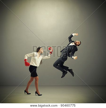 angry businesswoman in red boxing gloves punching businessman over dark grey background