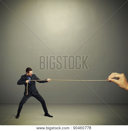 businessman in formal wear and big womans hand pulling the rope over dark grey background