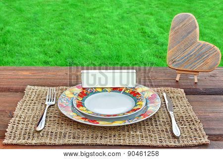 Picnic Table With Tableware, Wooden Heart And White Blank Signboard