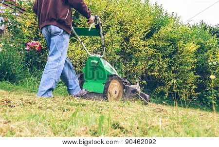 Senior man mowing the lawn with lawnmower