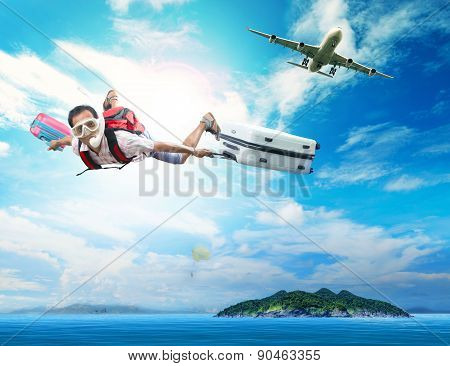 Young Man Flying On Blue Sky Wearing Snorkeling Mask And Holding Luggage Use For People Traveling By