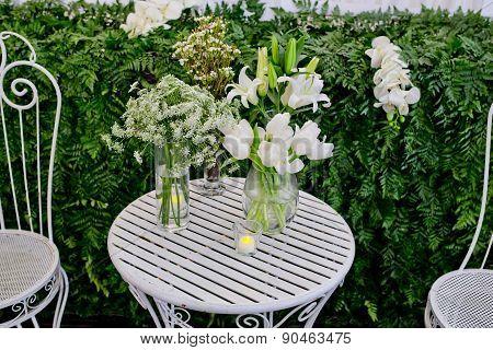 White Flowers Arrangement In Glass Vases On White Metal Desk.