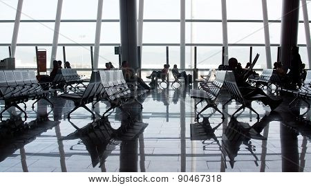 Airport interior large glass window and people reflected in shiny floor surface