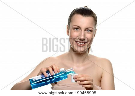 Smiling Young Woman Pouring Mouthwash Into A Cap