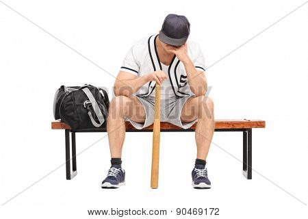 Sad young baseball player sitting on a bench and contemplating with his head down isolated on white background