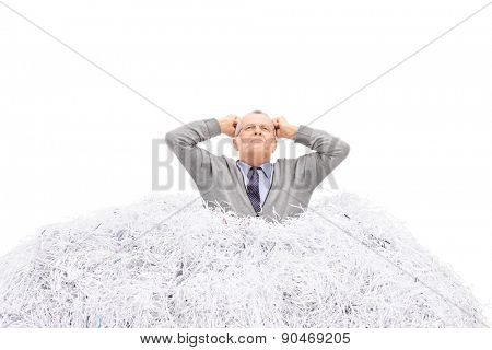 Senior man stuck in a pile of shredded paper, gesturing anger isolated on white background