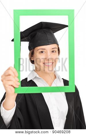 Vertical shot of a female student posing in graduation gown behind a green picture frame isolated on white background