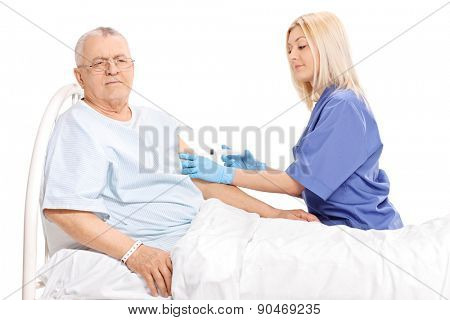Young female doctor giving an injection to a mature patient in a hospital bed isolated on white background