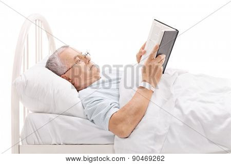 Mature patient reading a book and lying in a hospital bed covered with a white blanket isolated on white background