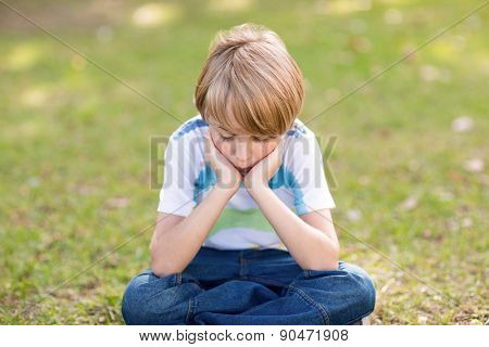 Little boy feeling sad in the park on a sunny day