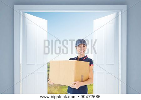Happy delivery woman holding cardboard box against scenic landscape