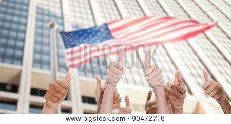 Thumbsup against american flag against sky scraper