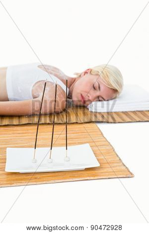 Attractive blonde woman resting on bamboo mat on white background