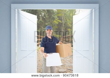 Happy delivery man holding cardboard box and clipboard against bridge with railings leading towards forest