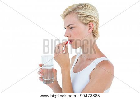 Pretty blonde woman holding glass of water and ready to swallow red pill on white background