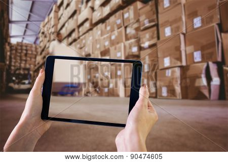 Finger pointing to tablet against worker with fork pallet truck stacker in warehouse