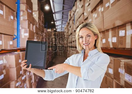Mature student pointing to tablet against shelves with boxes in warehouse