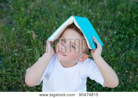 Little kid sitting on the grass playing with a book