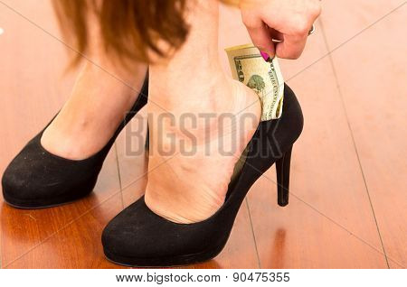 Superstitious woman's hand putting a dollar bill inside shoe