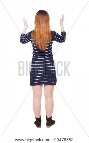 back view of woman. Young woman in vest presses down on something. Isolated over white background. Rear view people collection. backside view of person. She spread her arms out.