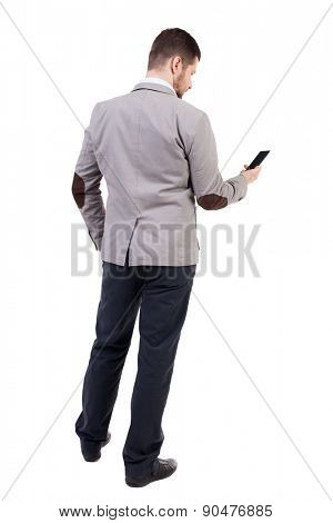 back view of business man in suit  talking on mobile phone.    rear view people collection. Isolated over white background. backside view of person. Businessman reading sms on the phone.