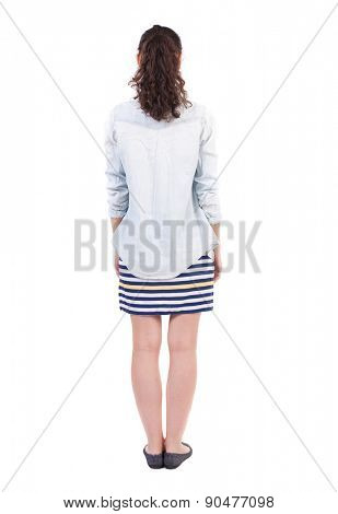 back view of standing young beautiful  woman. girl  watching. Rear view people collection.  backside view person.  Isolated over white background. curly girl in a striped skirt stands with her hands.