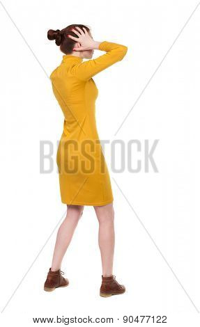Back view of shocked woman in dress .   upset young girl. Rear view people collection.  backside view of person.  Isolated over white background. A woman in a dress is shocked by what he saw.
