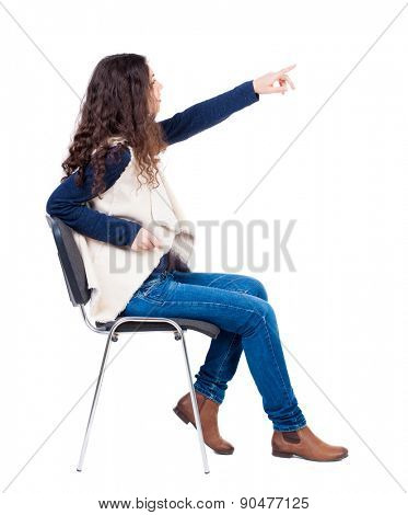 back view of young beautiful  woman sitting on chair and pointing.  girl  watching. Rear view people collection.  backside view of person.  Isolated over white background.