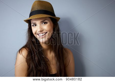 Portrait of beautiful young woman smiling happy, wearing straw hat.