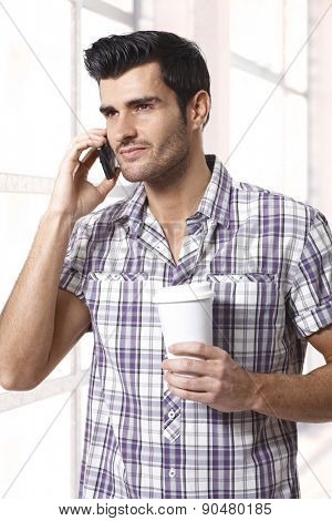 Handsome man on phone holding morning coffee.