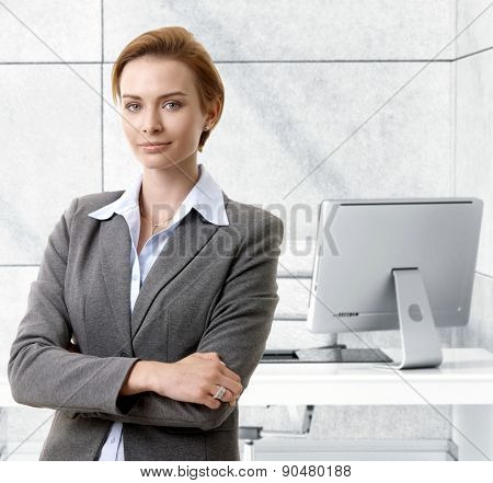 Confident caucasian businesswoman standing at office desk, smiling.