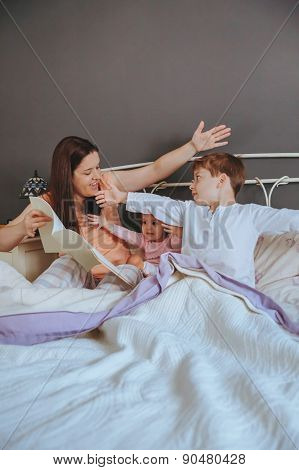 Mother reading book to her sons in the bed