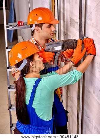 Happy family in builder helmet indoor. Drilled wall