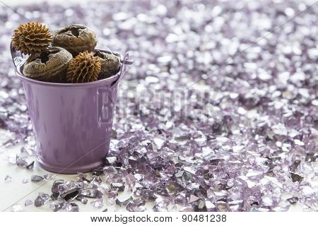 Purple bucket full of dry pine cones stands among violet shards of glass
