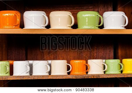 Colorful zinc cup on wooden shelves over wood background.