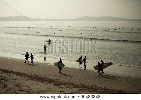 Sandy beach in the town of Weligama with lots of surfers in the sea and around