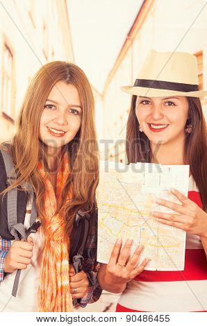 Two young girls travelling, holding a map
