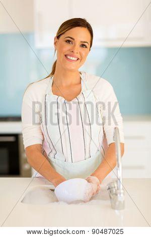 beautiful woman washing dishes in kitchen