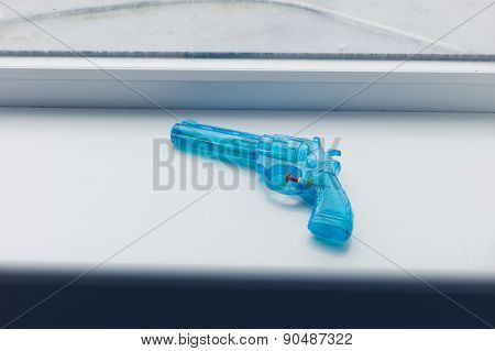 Blue Toy Gun On Window Sill