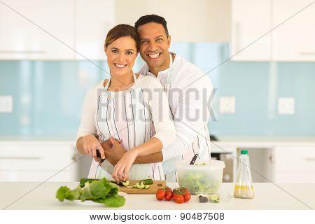 couple have fun in modern kitchen while preparing fresh vegetable salad