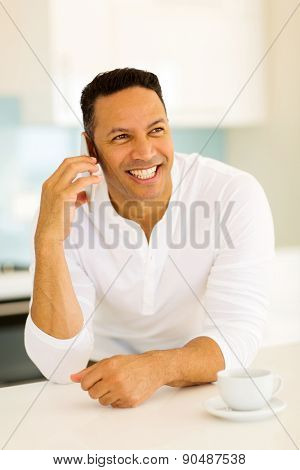 happy mid age man talking on cell phone at home
