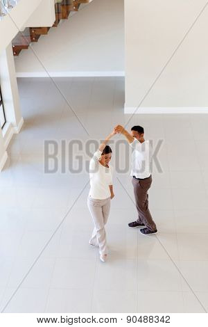 overhead view of couple dancing at their new home