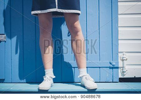 Woman Standing Outside Colorful Beach Hut