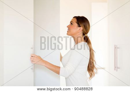 beautiful young woman opening wardrobe doors